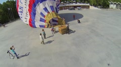 Stock Video Footage of People watch inflation of air balloon on square of park