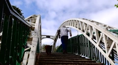 Man jogging with dog up the steps of an arched bridge Stock Footage