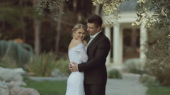 The groom in a suit hugging the bride in an elegant dress and she puts her head Stock Footage
