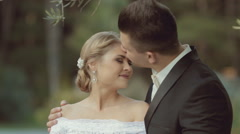 The groom gently kisses his beautiful bride, who laughs Stock Footage