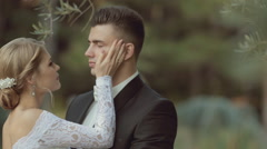 Wonderful bride gently stroking groom's face and kisses him in a wonderful park Stock Footage