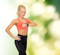 Smiling woman with heart rate monitor on hand Kuvituskuvat