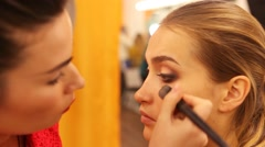 Master making make-up for a beautiful blonde Stock Footage