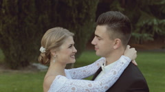 Charming bride smiling, laughing and kissing her groom, while standing on green Stock Footage