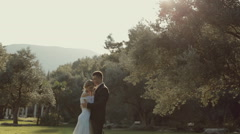 Handsome groom hugging his amazing bride while standing on green grass in the Stock Footage