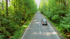 Car rides by road among trees with green leaves at summer Stock Footage