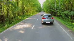 Car drives by road among trees with green foliage at summer Stock Footage