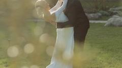 Stylish brunette groom tilts his slender bride and kisses her Stock Footage