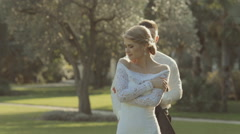 Handsome groom comes  to bride behind her and puts on his jacket Stock Footage