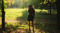 Silhouette of girl in hat in autumn park Stock Footage