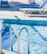 A swimming pool with sun loungers Stock Photos