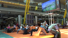 Barajas airport sitting area with departure screens Stock Footage