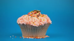 Small dragees pour on beautiful cake, on a blue background Stock Footage