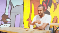 Man sits at outdoor cafe picnic table in front of a mural and eats a scone Stock Footage