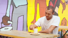 Man sits at outdoor cafe picnic table in front of a mural and drinks coffee Stock Footage