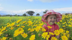 Small child playing in a meadow full of flowers. Spain.  Clip 1b. Stock Footage