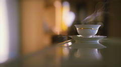 Vintage porcelain teacup with hot tea on a glass desktop. Orange tint. - stock footage