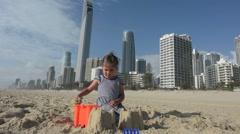 Little girl builds sand castle in Surfers Paradise Australia Stock Footage