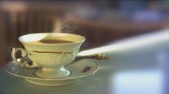 Closeup of a vintage porcelain teacup with hot tea on a glass desktop. - stock footage