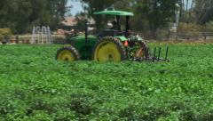 Tractor working in farm field - stock footage