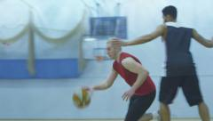 Basketball player gets past defender and slam dunks in slow motion Stock Footage