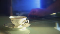 Person using a laptop, with a teacup in the foreground. Shallow focus. Stock Footage