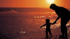 Mother and daughter playing by the sea at the sunset. Calblanque, Murcia, Spain. Stock Footage