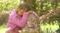 Small girl by a stone lion in the garden. Stock Footage