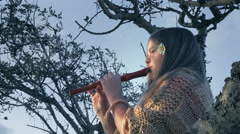 Girl plays a flute sitting on a tree. Stock Footage