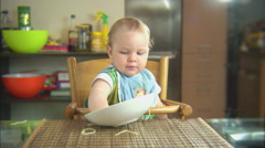 Funny child playing with spaghetti and sauce. Scene 4 Stock Footage