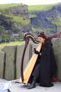 Woman playing the harp for tourists. Cliffs of Moher - stock photo
