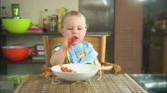 Funny child playing with spaghetti and sauce. Scene 5 Stock Footage