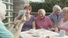 4K Happy group of senior friends pose to take a picture with computer tablet - stock footage