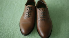 Brown leather shoes on a green background Stock Footage