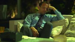 Attractive businessman yawning and sleeping on sofa at home at night HD Stock Footage