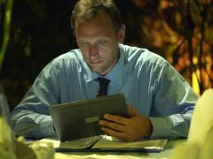 Businessman working on tablet computer sitting by table at night NTSC Stock Footage