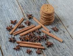 cinnamon sticks, star anise and gingersnap cookies on rustic wood background - stock photo