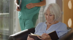 4K Caring male nurse giving support to elderly female patient in care home - stock footage