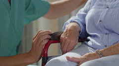 4K Close up caring nurse holding hand of elderly female patient in a wheelchair Stock Footage