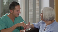 4K Caring male nurse giving support to elderly female patient in care home Stock Footage