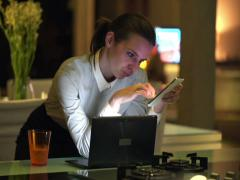 Bored, lazy businesswoman sitting by counter in kitchen at night NTSC Stock Footage