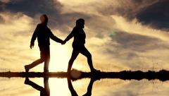 Young couple holding hands walking together outdoors. strong relationship symbol Stock Footage