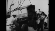 Military jeep being loaded on warship at harbour of south coast Stock Footage