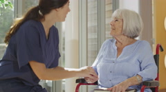 4K Caring nurse giving support to elderly female patient in care home Stock Footage
