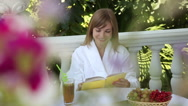 Stock Video Footage of Young adult reading a book and smiling at the camera. Girl sitting at a table