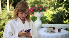 Young adult in a bathrobe on the front porch. She holds a mobile phone Stock Footage