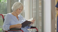 4K Caring nurse giving support to elderly female patient in care home - stock footage