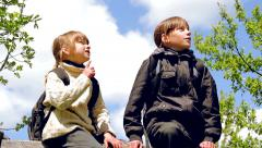 Two boys with backpacks sitting on the fence, watching the sky. Stock Footage