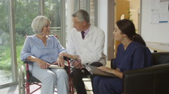 4K Caring doctor and nurse discussing medical notes with elderly female patient - stock footage