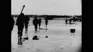 Allied soldiers walking on beach Stock Footage